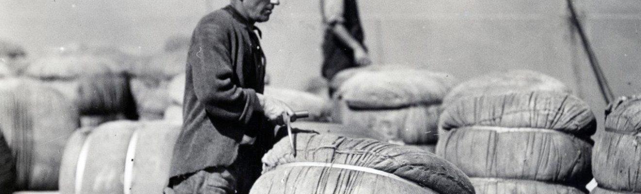 Man hauling bale of wool